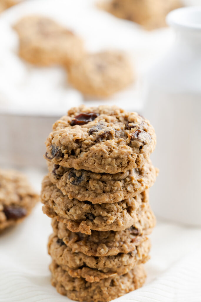 Stacked oatmeal raisin cookies with white background.
