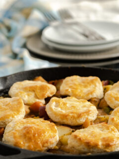 Turkey pot pie in cast iron skillet topped with biscuits.