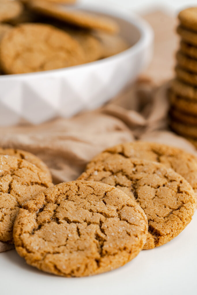 Close up of chewy gingersnap cookies with a white bowl in the background.