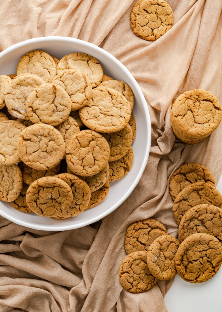 Gingersnap cookies in white serving bowl with cookies spread around the bowl.