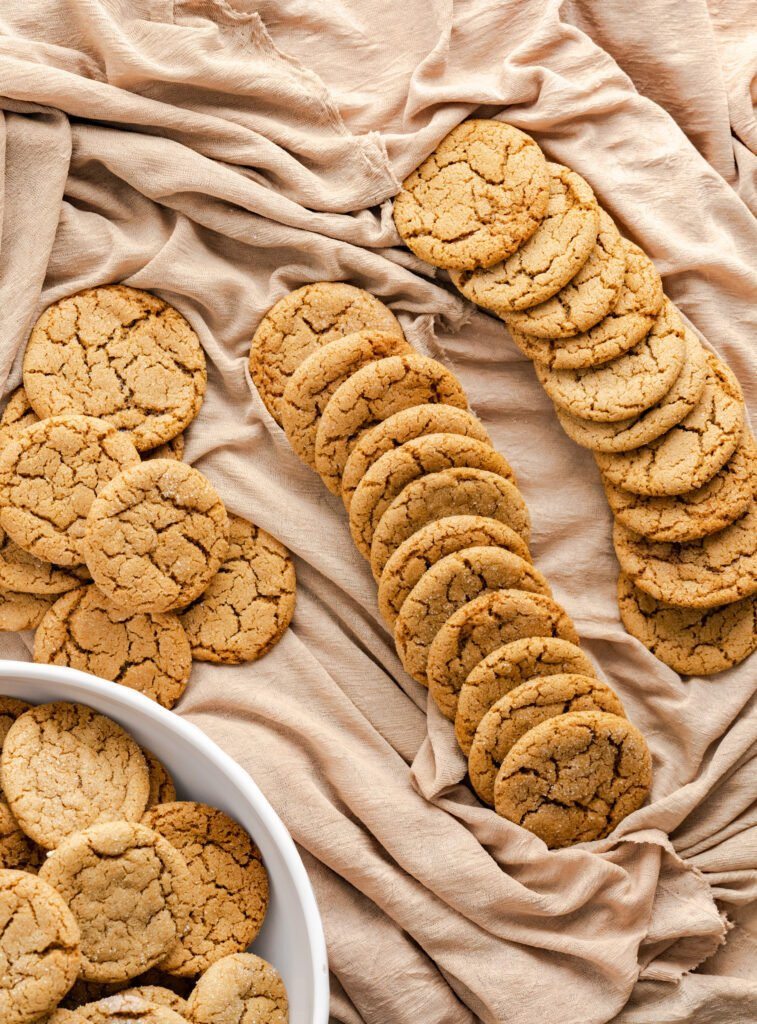 Two rows of gingersnap cookies and cookies in a white bowl.