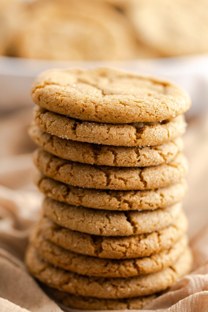 10 chewy gingersnap cookies stacked in center and sitting on brown fabric.