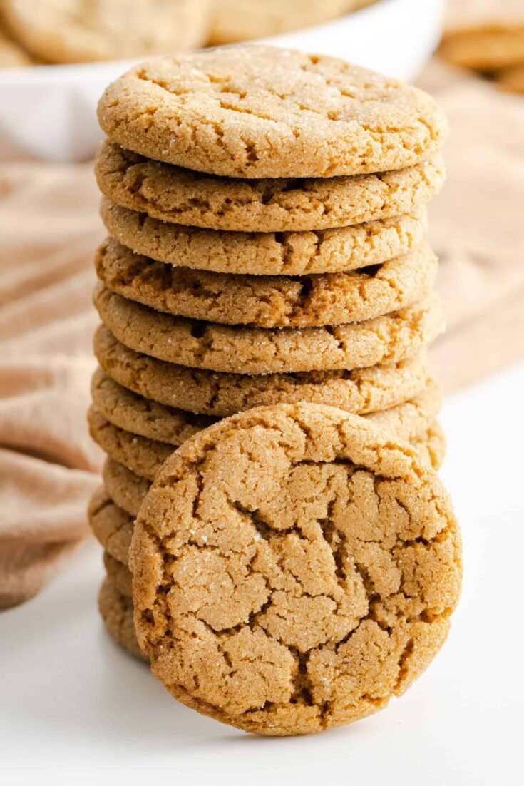 Stacked chewy gingersnap cookie rolled in granulated sugar with a cookie propped in front.