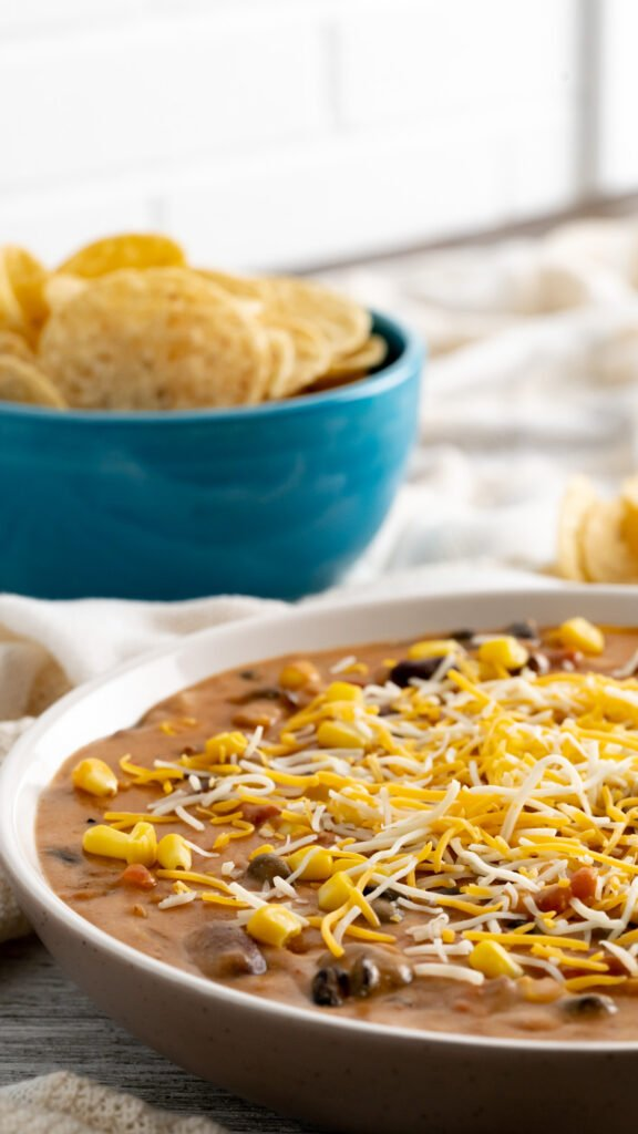 Side view of taco dip in serving bowl topped with shredded cheese and corn.