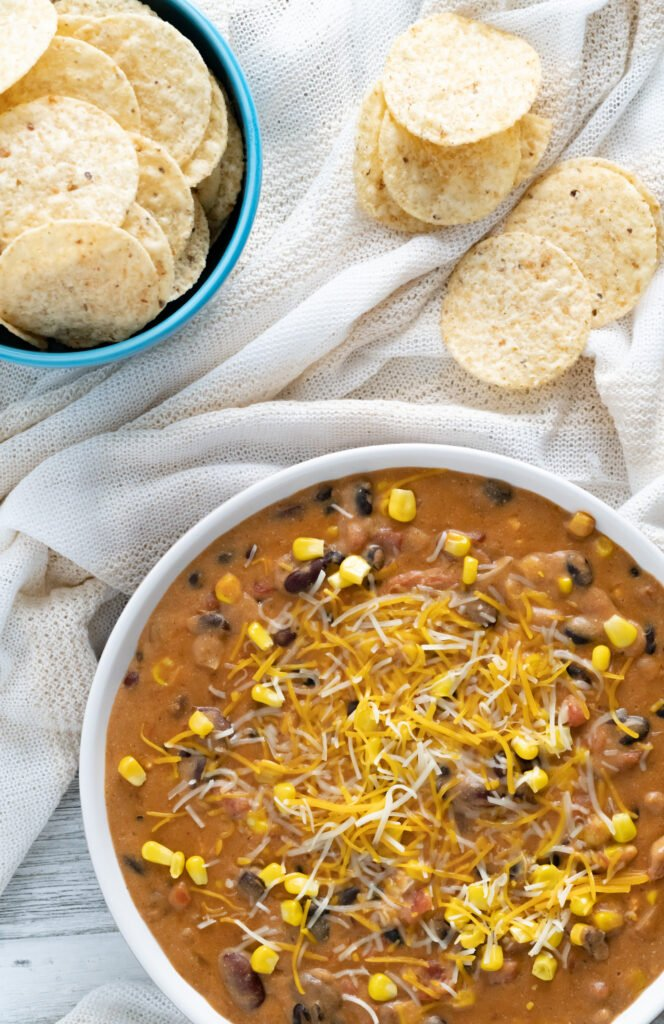 Instant Pot Taco Dip served with tortilla chip rounds in blue bowl.