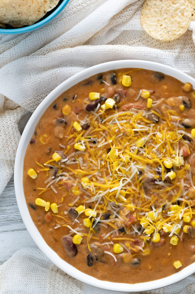 Tacco dip topped with cheddar cheese and super sweet corn on gray background.