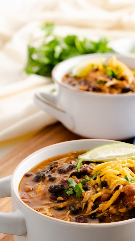 A bowl of Instant Pot Chipotle Chicken chili served with shredded cheese, sliced lime, and cilantro.