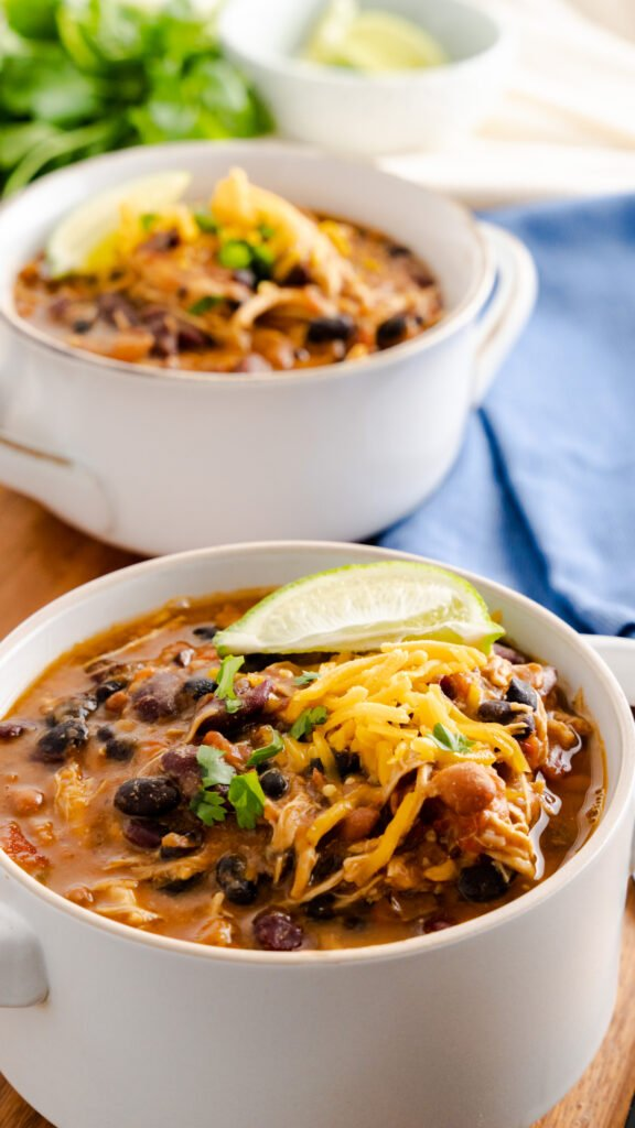 Chicken chili topped with shredded cheese and lime wedge.