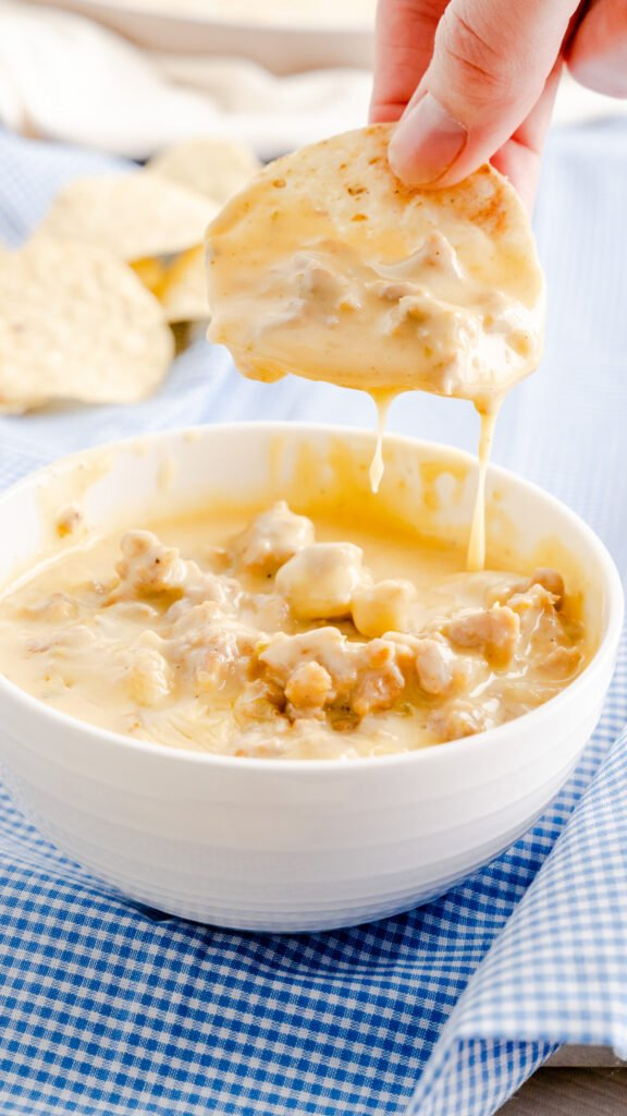 Tortilla chip scooped with sausage queso dip with cheese dripping into bowl.