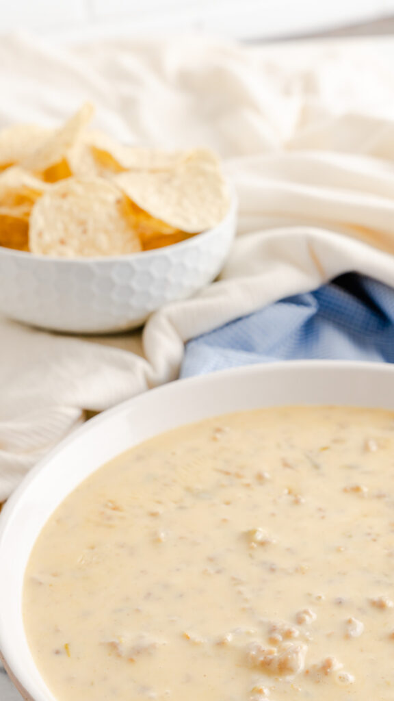 White serving bowl of instant pot cheese dip made with sausage on blue checkered napkin.