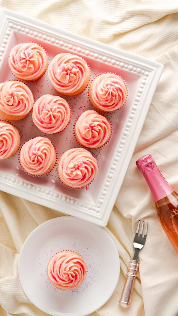 Pink champagne cupcakes served on square platter and on white saucer.