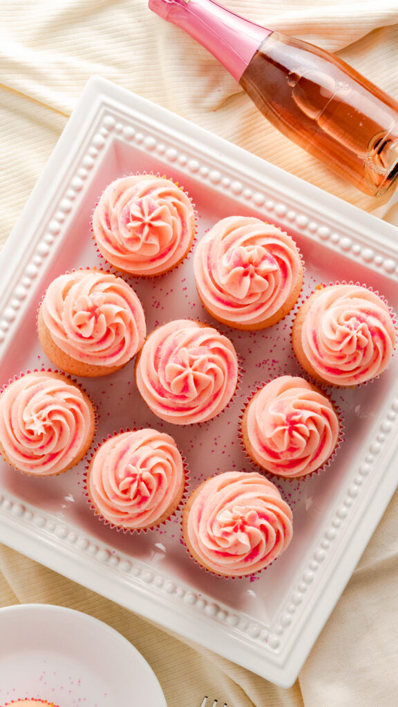 Pink champagne cupcakes on decorative square serving platter served with bottle of pink champagne.