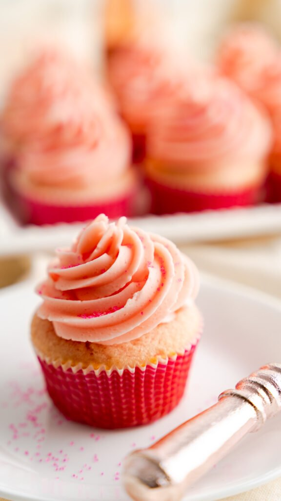 Pink champagne cupcake on white saucer and served with fork.