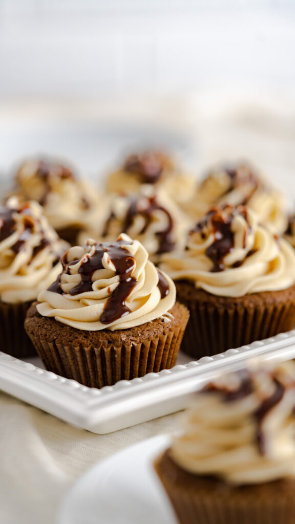 Ganache topped chocolate gingerbread cupcakes on a white serving platter.