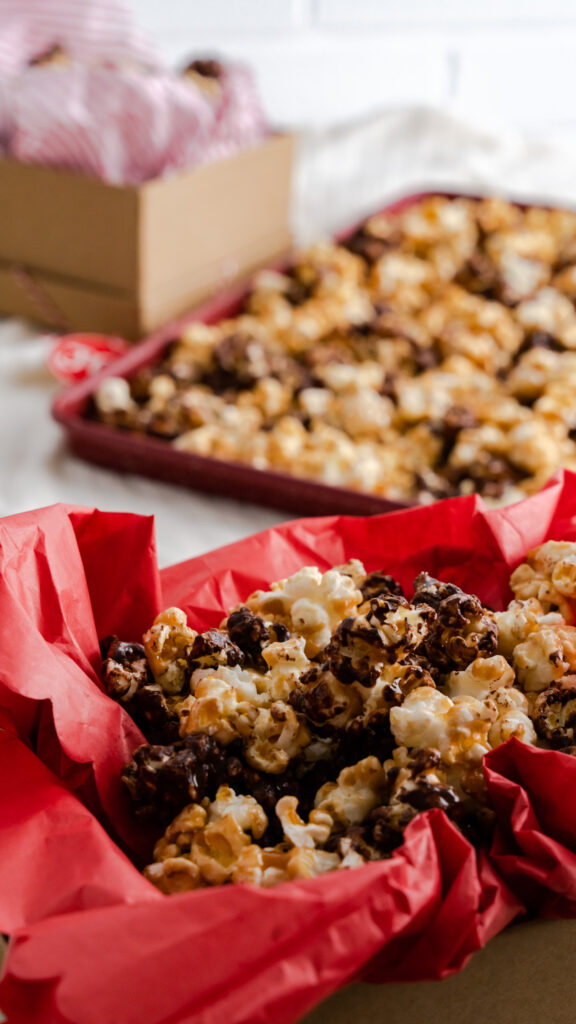 Christmas gift box filled with red tissue paper and caramel popcorn