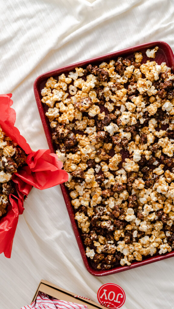 Popcorn on red baking sheet and gift boxes.