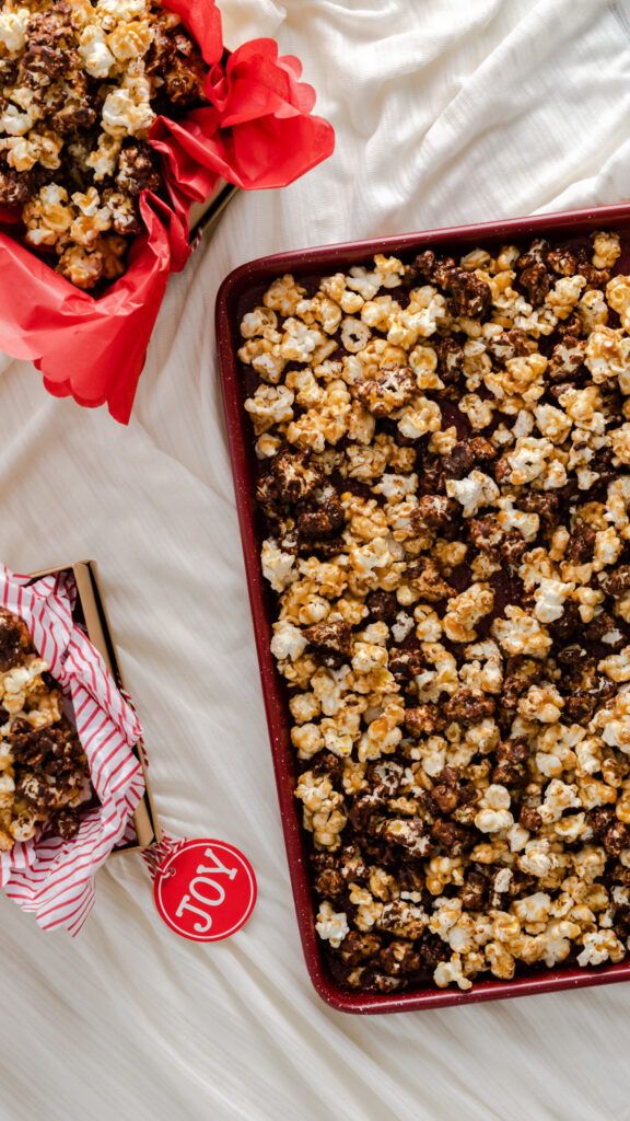 Chocolate caramel popcorn on red baking sheet with gift boxes filled with popcorn.