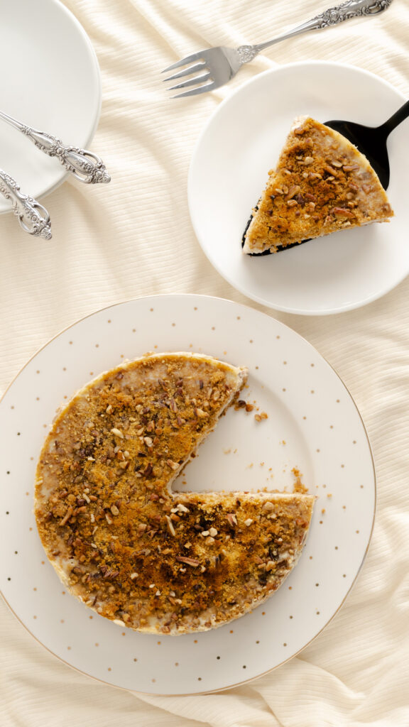 Slice of butter pecan cheesecake beside serving with cheesecake topped with pecans.