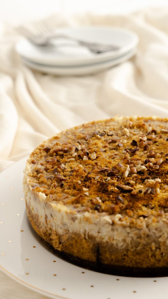 A 7 inch instant pot butter pecan cheesecake sitting on a decorative plate.