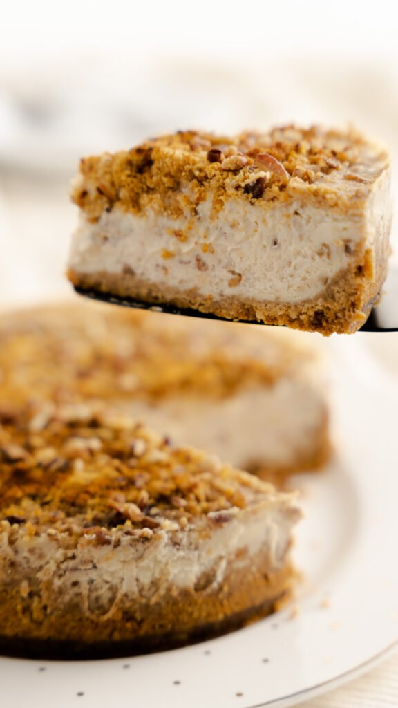 Slice of butter pecan cheesecake on black cake server being held above sliced cheesecake.
