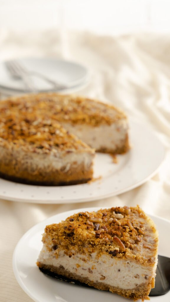 A butter pecan cheesecake slice topped with graham cracker crumbs and chopped pecans.