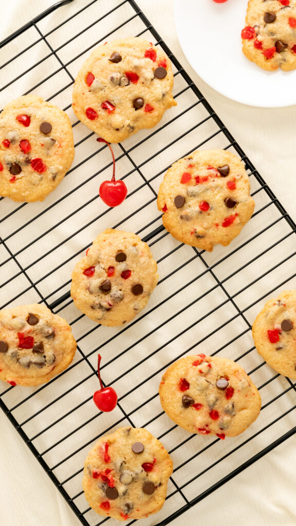 Cherry chocolate chip cookies on black wire rack.