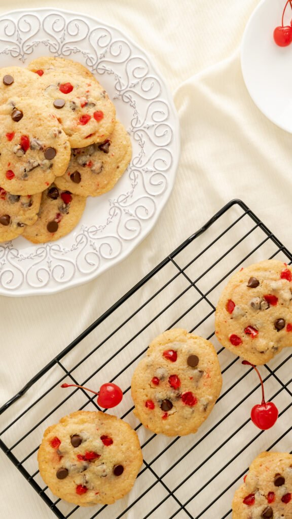 Cherry chocolate chip cookies on wire rack and cookies stacked on decorative white plate.