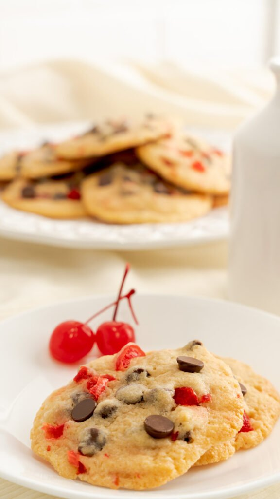 Two cherry chocolate chip cookies for valentine's day on a white plate with maraschino cherries.