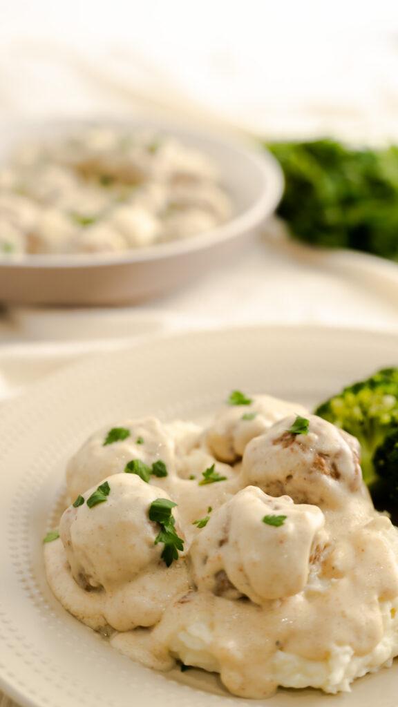 IKEA Copycat Swedish meatballs on beige plate with mashed potatoes and broccoli.