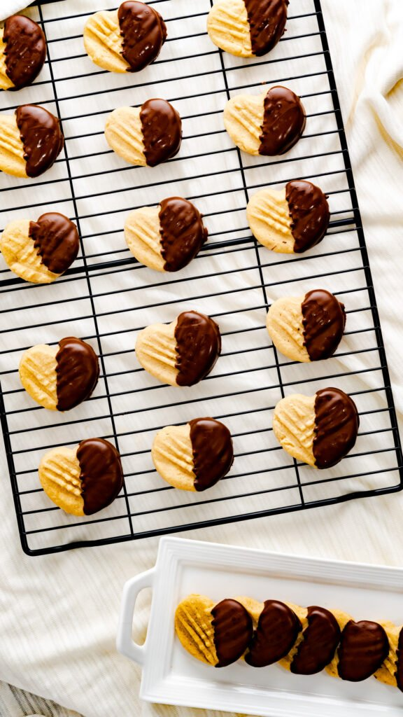 Heart Peanut Butter Cookies dipped in chocolate on black cooling rack and on white rectangular serving platter.