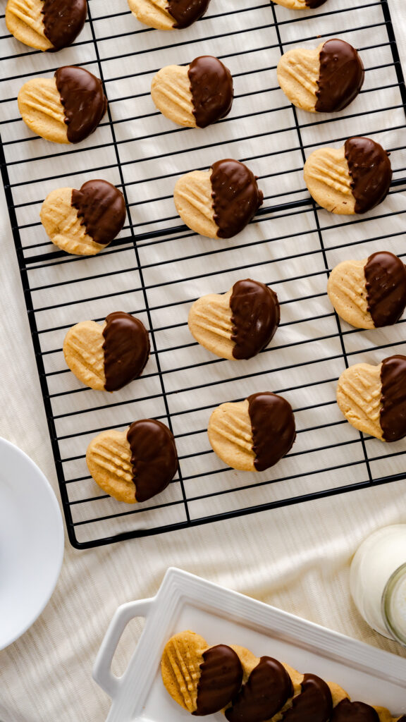 Heart shaped peanut butter cookies dipped in chocolate and set on a black cooling rack.