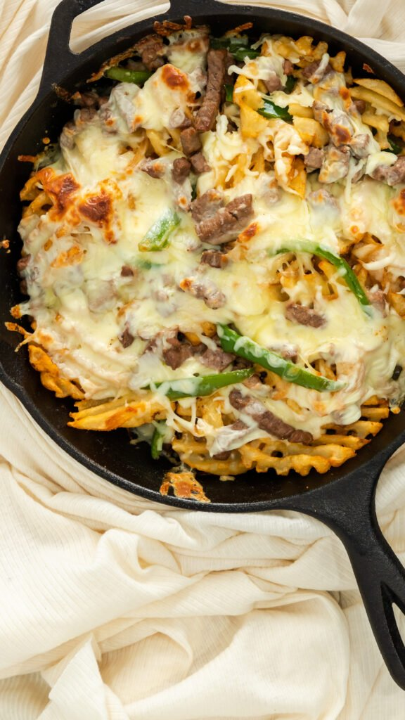 Close up of Philly steak and cheese fries in cast iron skillet.
