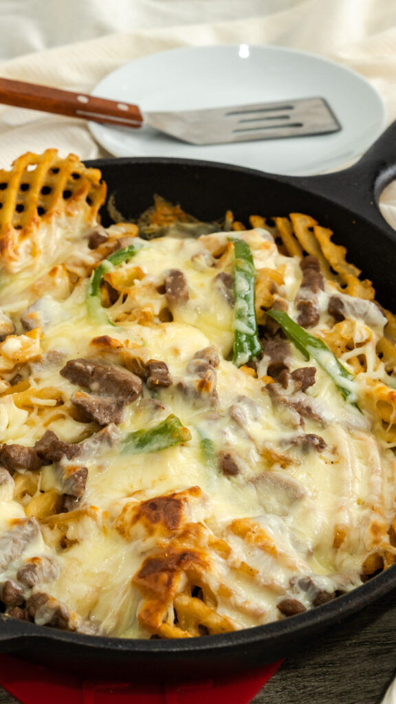 Cast iron skillet of Philly steak and cheese fries.