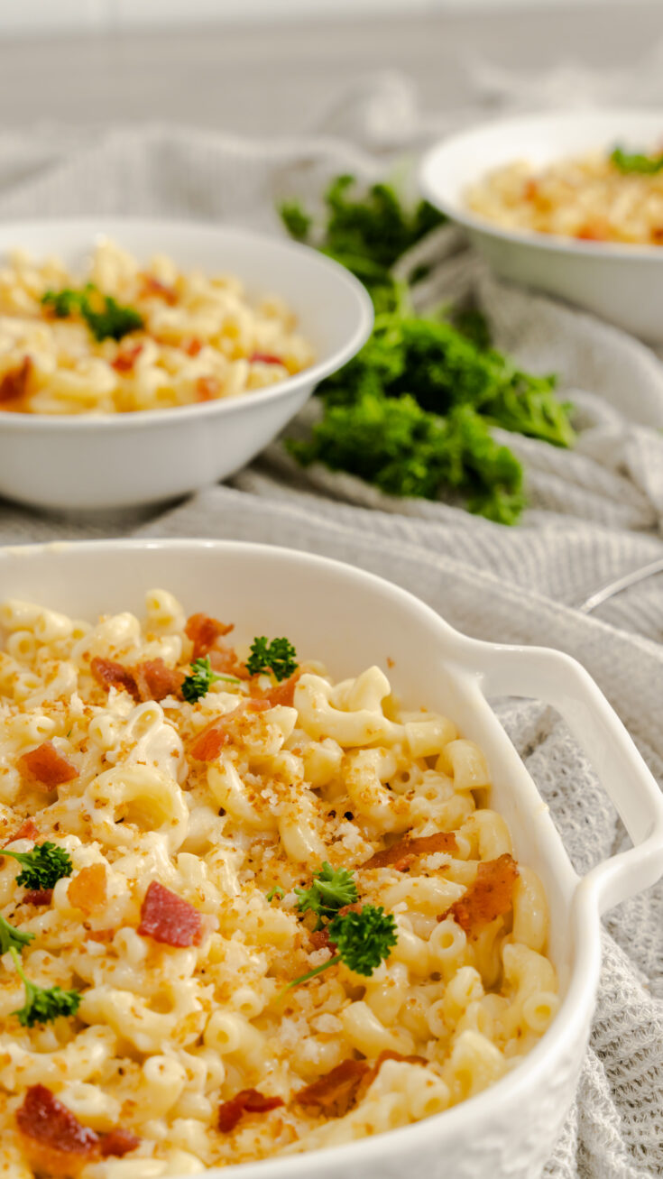 Irish Mac and Cheese garnished with panko crumbs, bacon, and parsley in white serving bowl