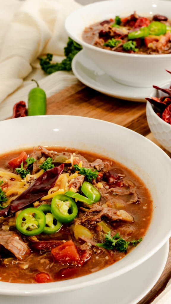 Instant Pot Spicy Venison Chili garnished with serrano peppers, cheese, and chile de arbol.
