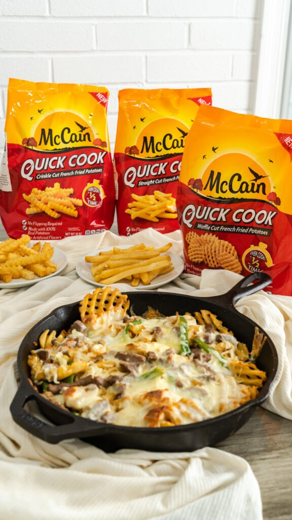 McCain Quick Cook Fries sitting behind cast iron skillet with philly steak cheese fries.