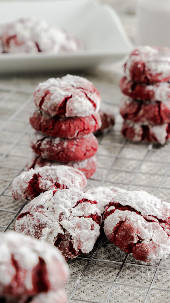 Confectioner sugar coated crinkle cookies on wire rack.