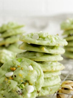 stack of pistachio cookies with cookie propped in front