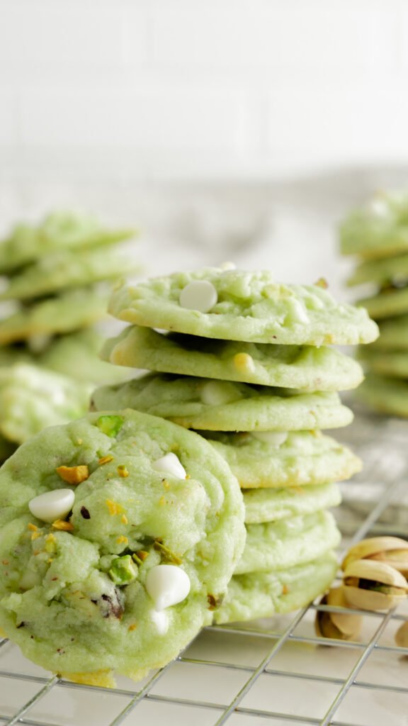 Stack of pistachio cookies with cookie propped in front sitting on wire rack.