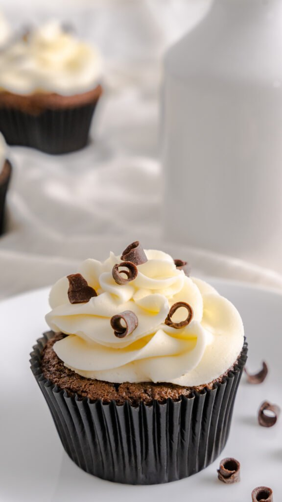 One chocolate cupcake topped with white buttercream and chocolate curls on white plate.