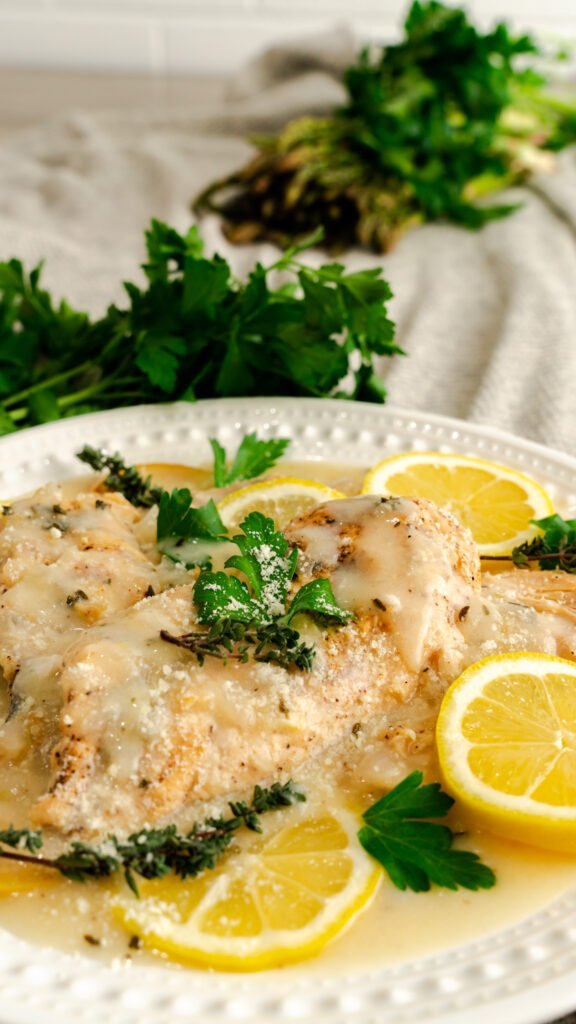 Instant Pot Parmesan chicken served with fresh lemons, parsley, and thyme.