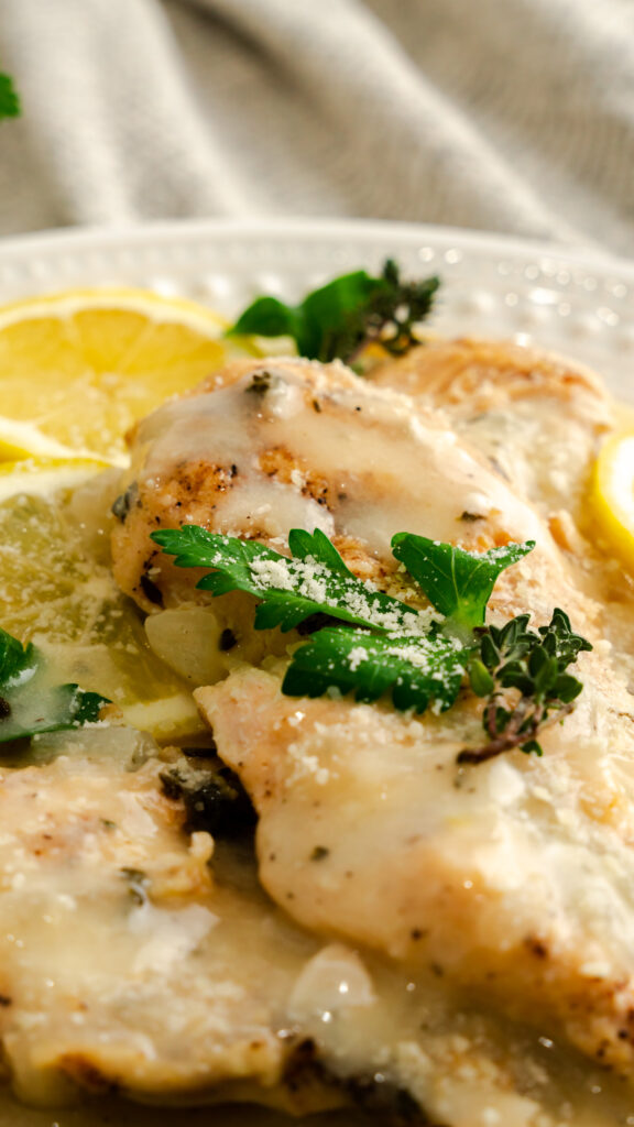 Close up of instant pot lemon thyme parmesan chicken topped with Parmesan and Parsley.