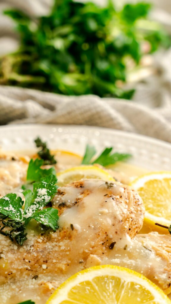 Instant Pot Parmesan Chicken with lemon served with lemon slices and fresh thyme and parsley.