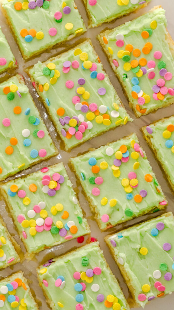 Top view of sugar cookie bars with green frosting with marble background.