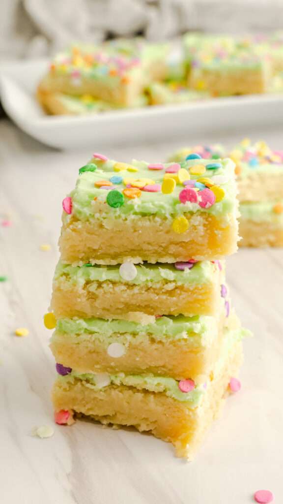 Four sugar cookie bars stacked with green icing and colorful sprinkles.