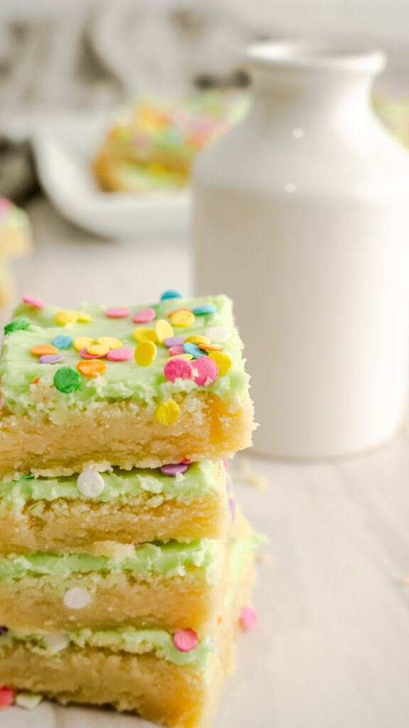 Sugar cookie bars with pastel color confetti sprinkles stacked four high.