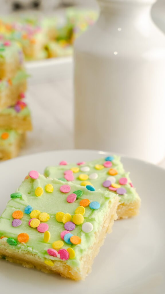Two sugar cookie bars decorated with confetti sprinkles on white plate.
