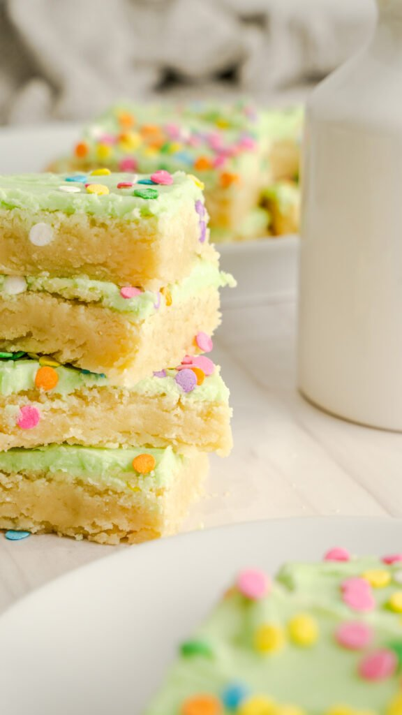 Green frosted sugar cookie bars with white milk jug In background.