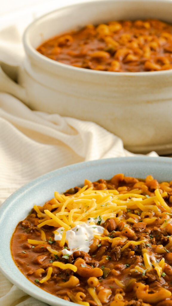 Bowl of chili mac with shredded cheese and sour cream.
