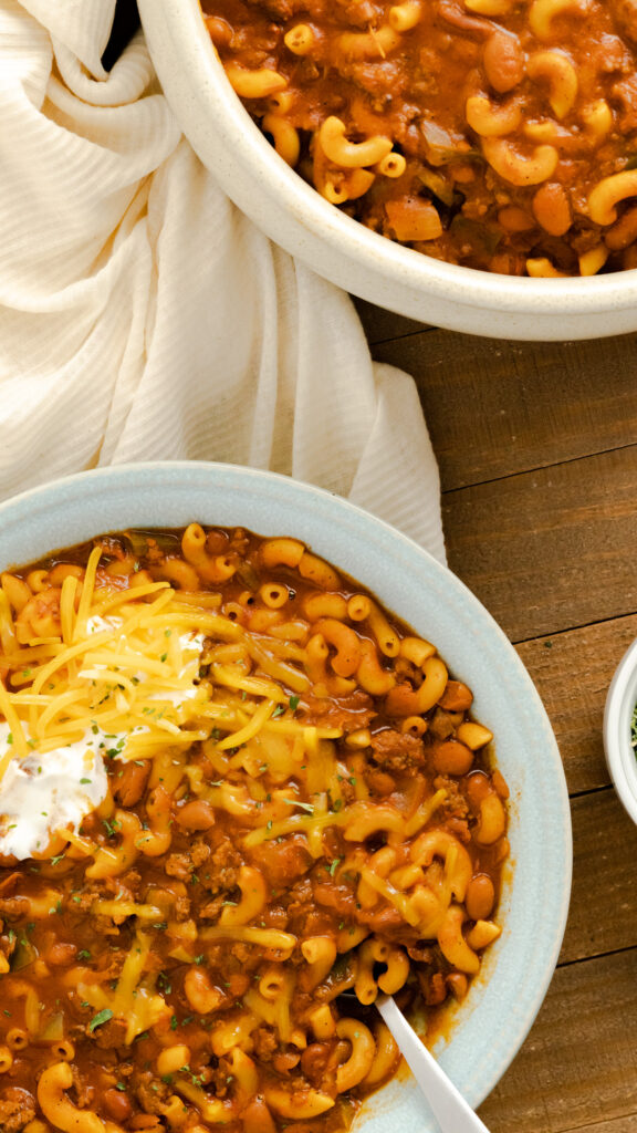Two bowls of instant pot chili mac with sour cream and cheese.